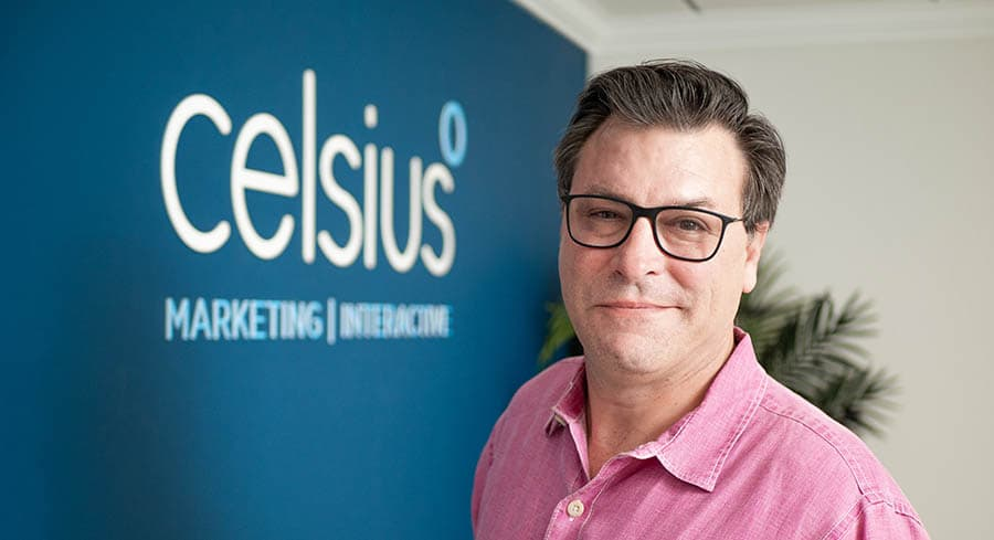 Photo of CEO and founder JP Smith, standing in front of the Celsius logo in the front lobby.